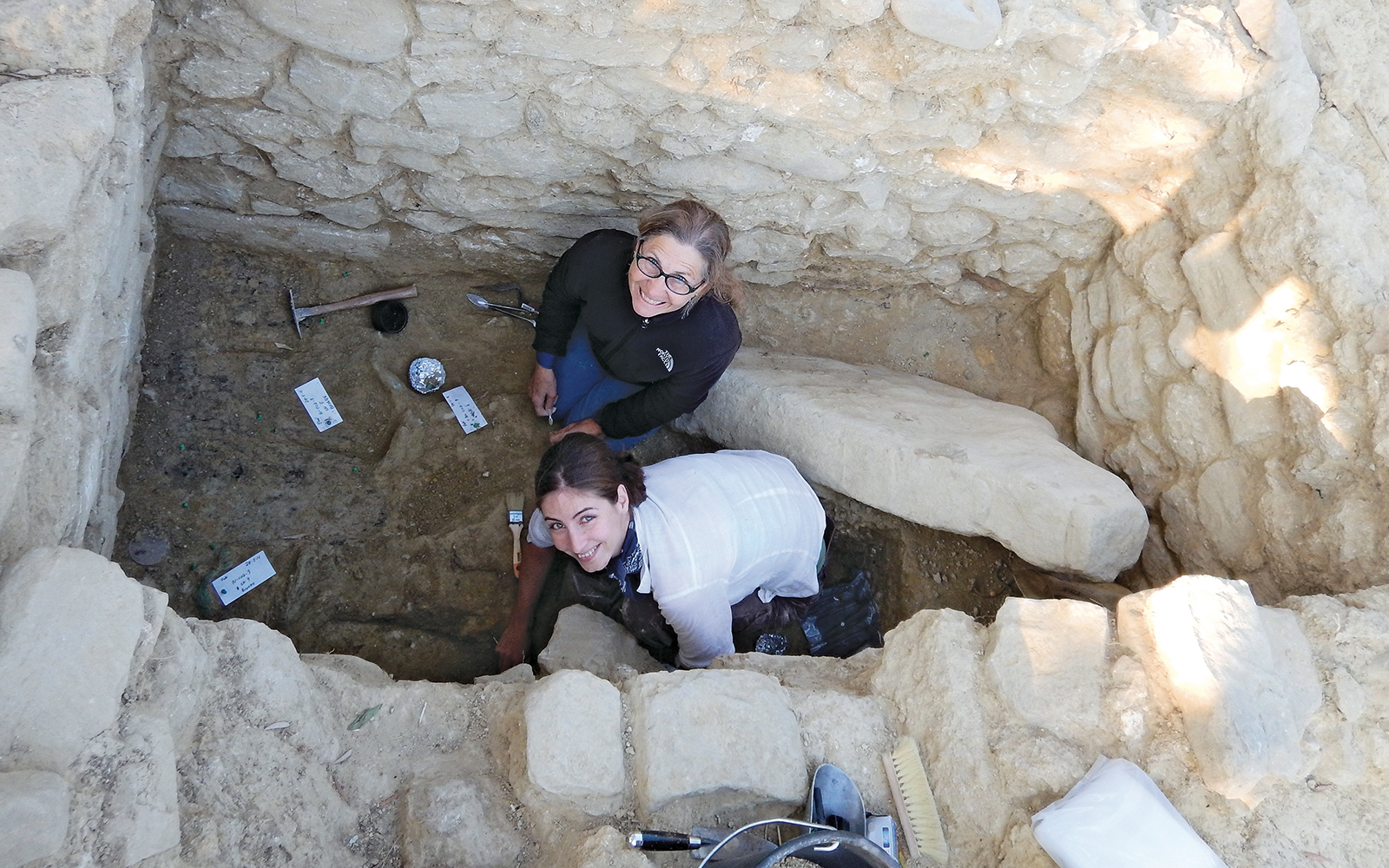 Stocker (top) and colleague Jonida Martini excavate the upper layer of artifacts immediately after bronze was discovered in the tomb.