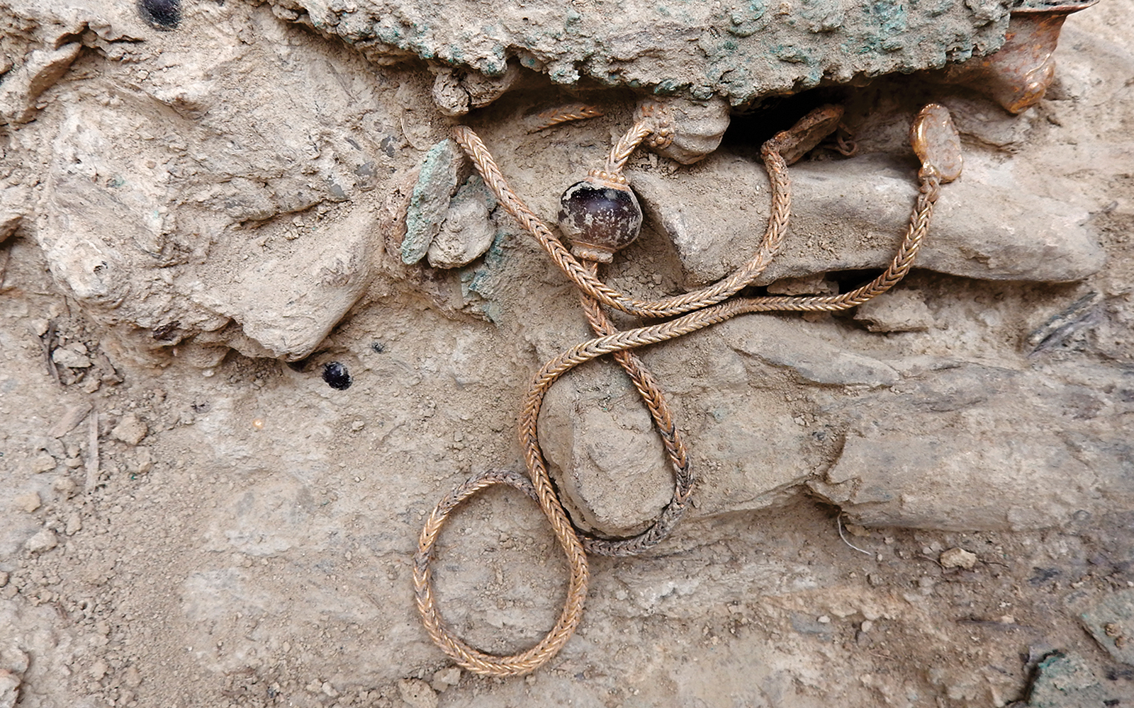 More treasures from the tomb: a gold necklace before removal (top).
