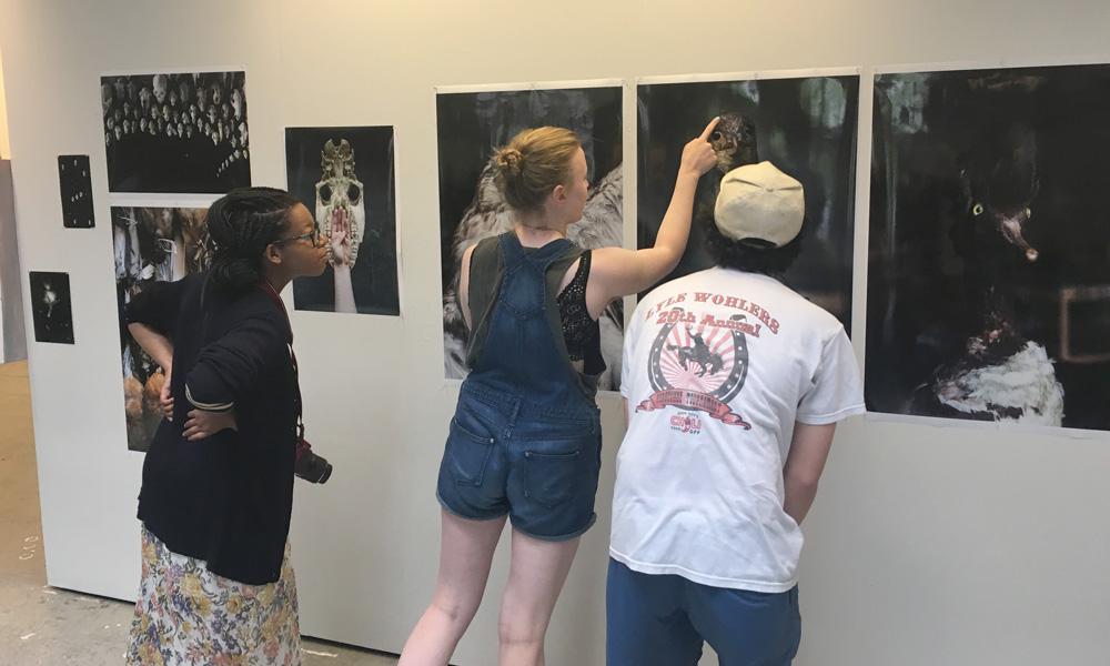 Ivy Distler, Matt Dumon, Hollie Davis in a group critique looking at Ivy's photographic work