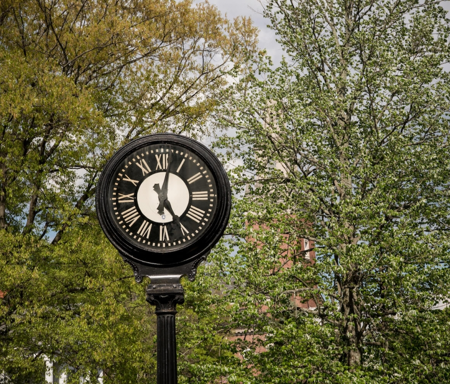 Clock on Denison campus with trees in background