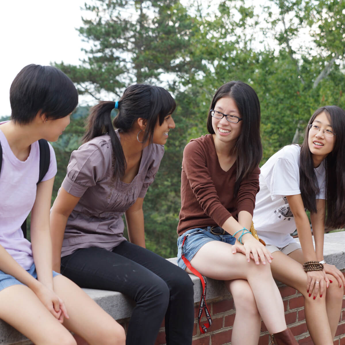 International students sitting on Denison's Academic Quad talking.