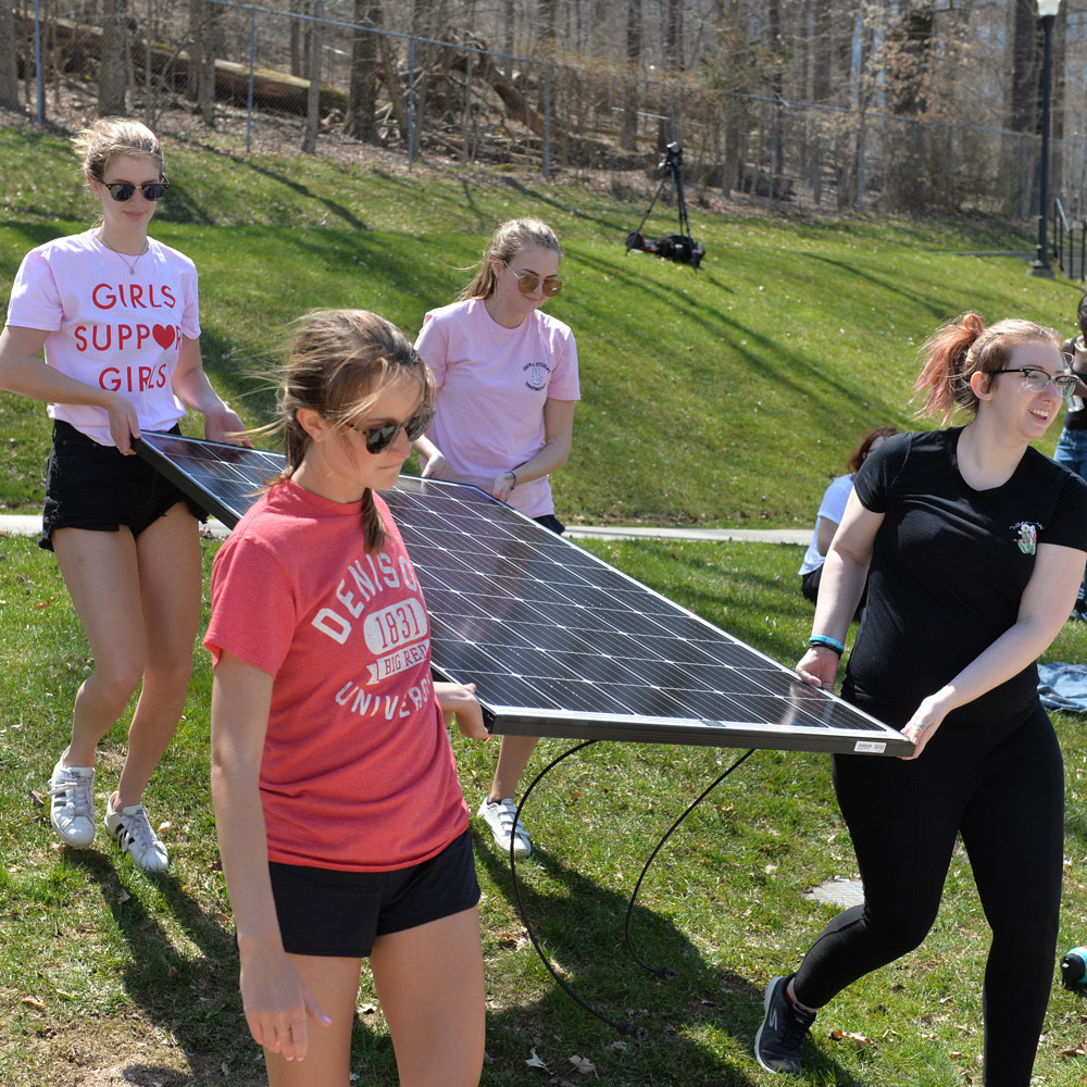Students carrying a solar panel
