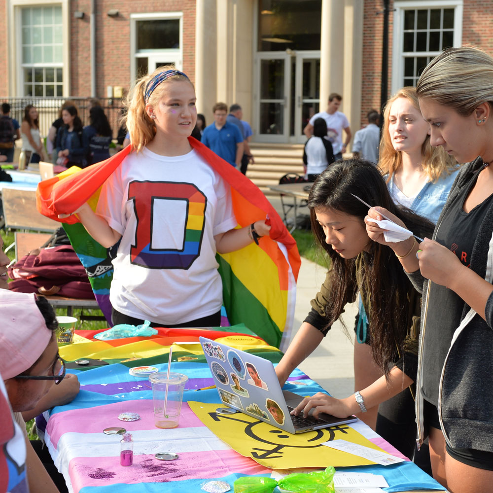 Student with pride flag at the involvement fair