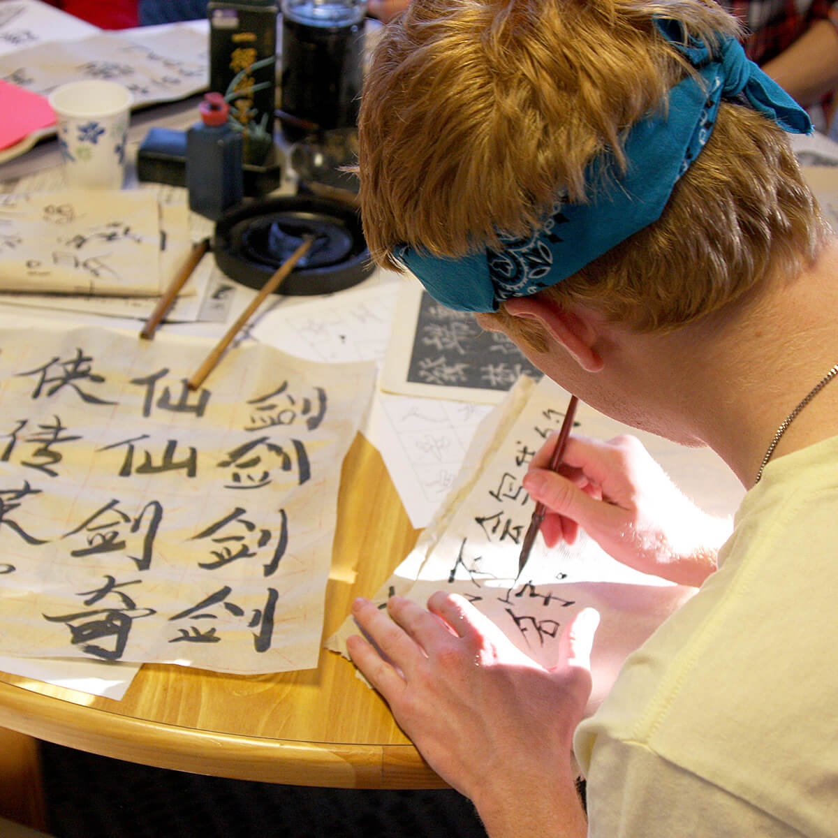 Picture of a student writing Chinese with a brush and ink.