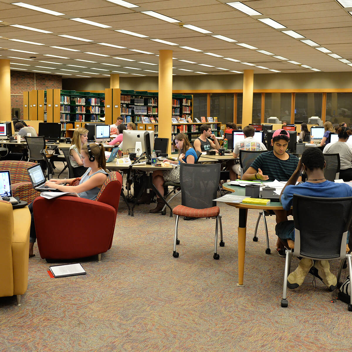 A large group of students studying and working in the library.