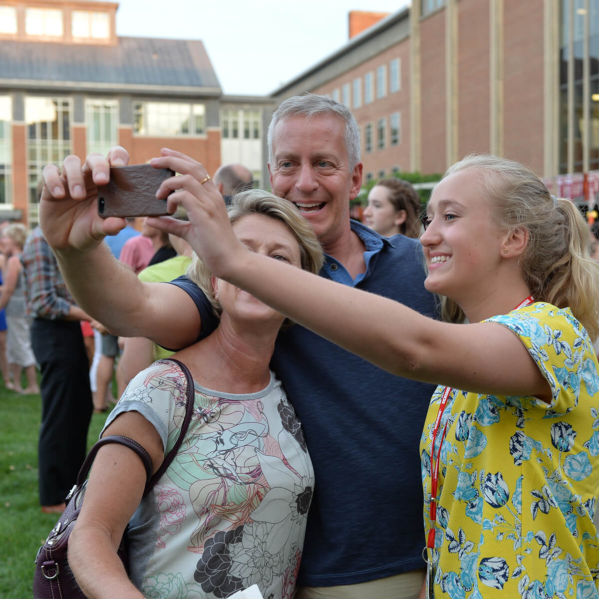 A mother, father, and daughter taking a selfie with a cellphone during Move In Day at Denison University.