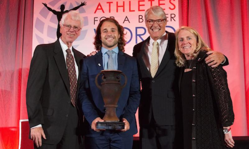 Luke Romick '16 posing on stage with three presenters of his Wooden Cup Award