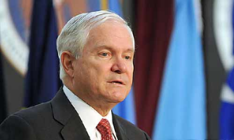 Robert Gates speaks with colorful flags in the background