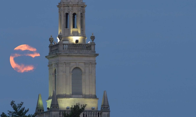 Swasey Chapel at night with a full moon in the background