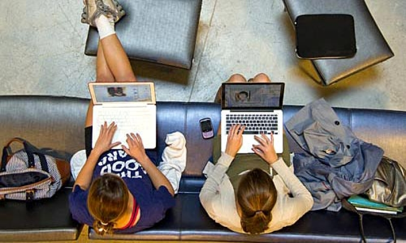 A view from overhead of students studying with laptops