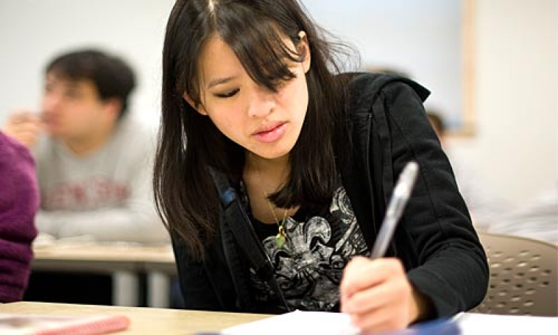 A student writes with a pen