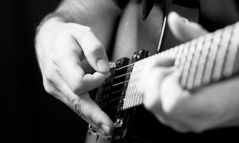 Close-up of a person playing the guitar