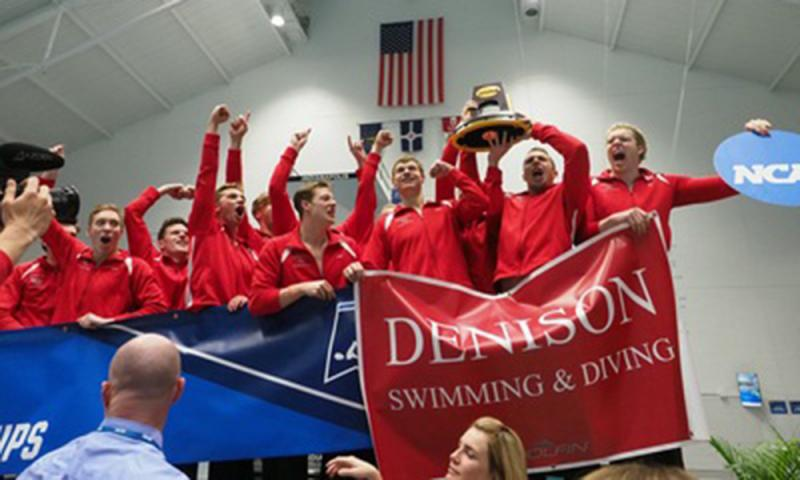 Men's swim and dive team with trophy and banner