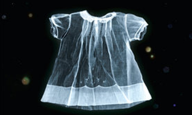 Photo of a child size dress against a black background