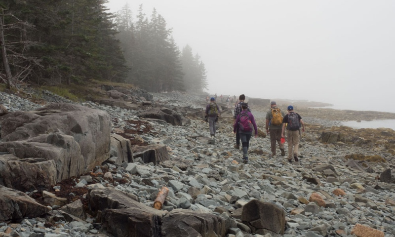 Students walking away from the camera on the rocks
