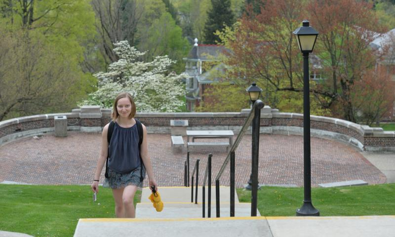 student walking up stairs with trees in the background