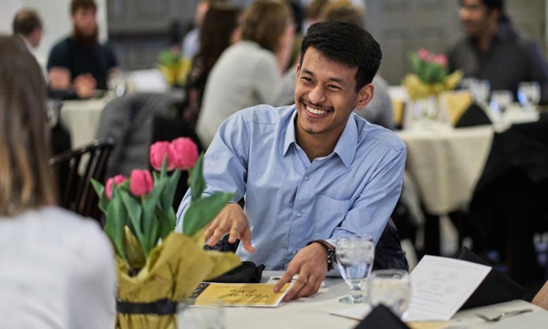 student smiling during dinner