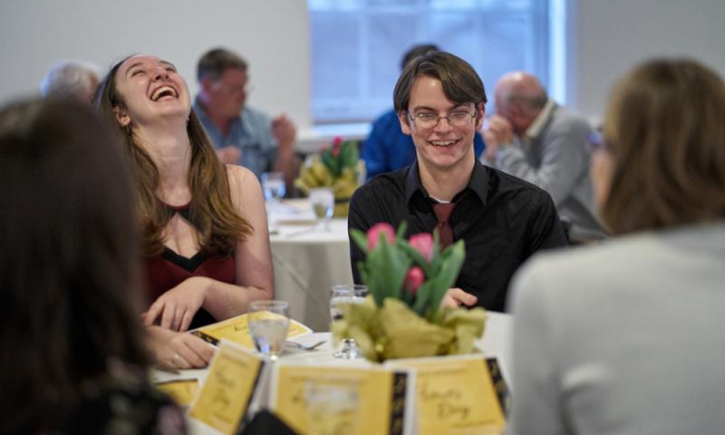 Students laughing around a dinner table