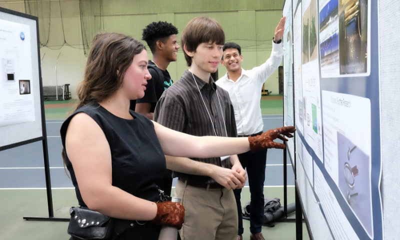 Students pointing at research posters