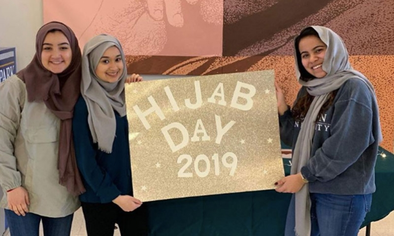 Students holding Hijab Day 2019 sign