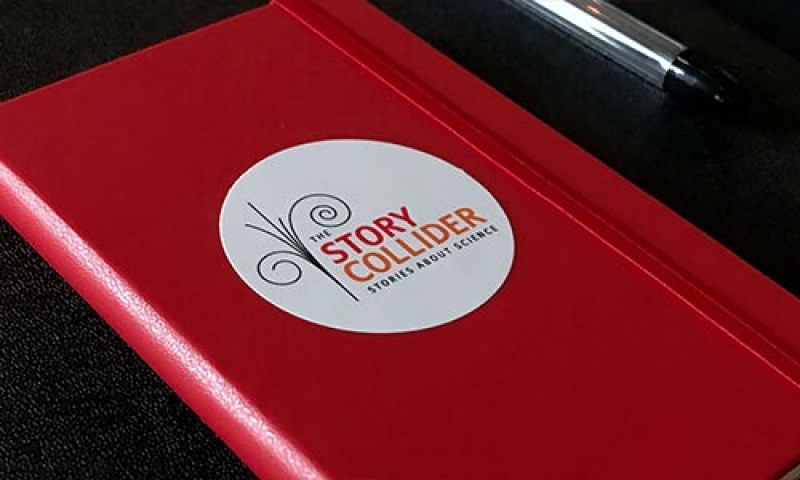 "Photo of a red notebook that says ""The Story Collider"" on it"