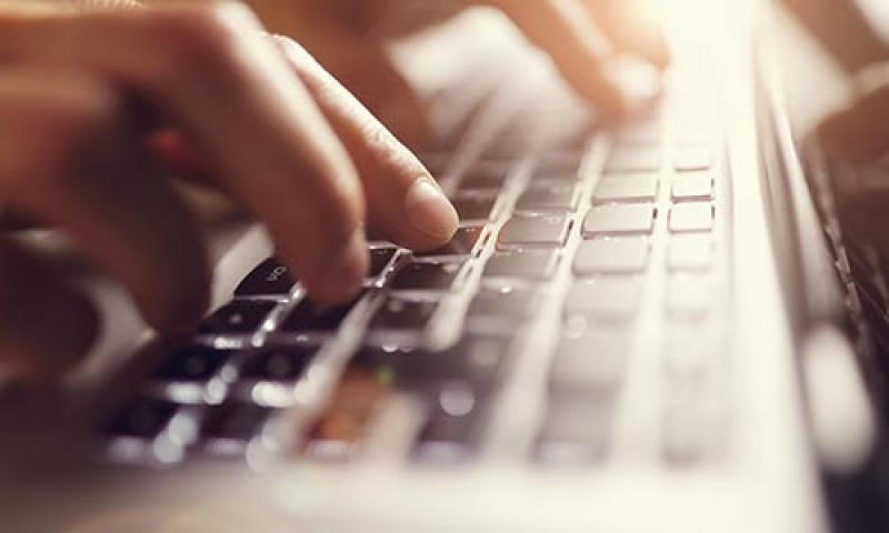 Photo of hands typing on a keyboard