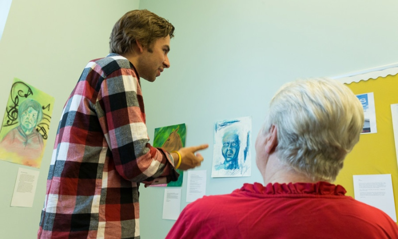 Student describing his art work to a resident of Flint Ridge Nursing and Rehabilitation Center