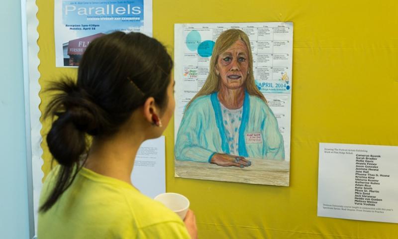 Student viewing art work of a nurse of Flint Ridge Nursing and Rehabilitation Center