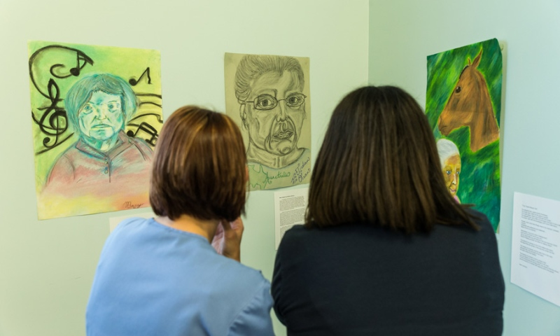 Nurses of Flint Ridge Nursing and Rehabilitation Center viewing artwork and reading their description
