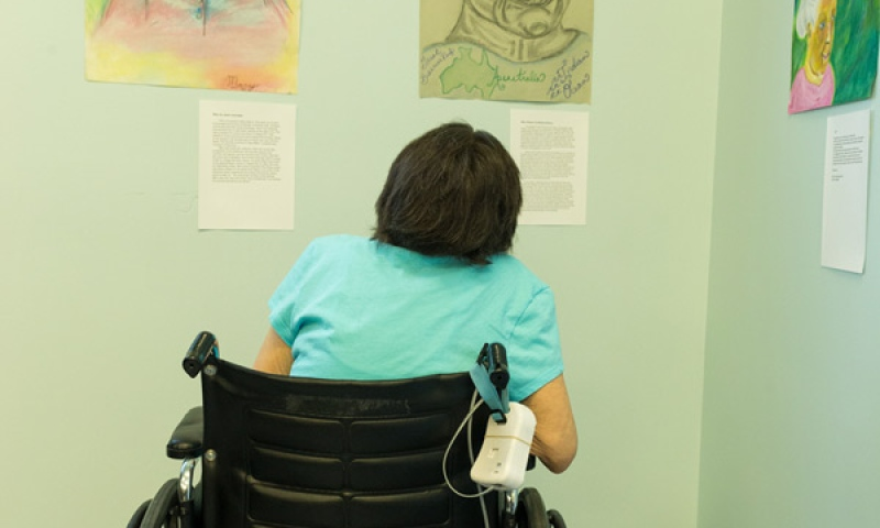 Resident in wheelchair of Flint Ridge Nursing and Rehabilitation Center viewing the artwork
