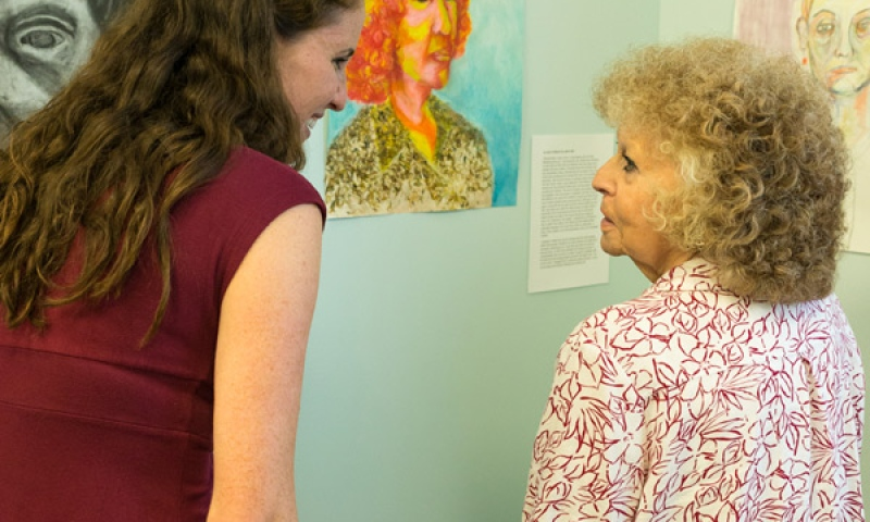 Student and Resident smiling while viewing art at Flint Ridge Nursing and Rehabilitation Center