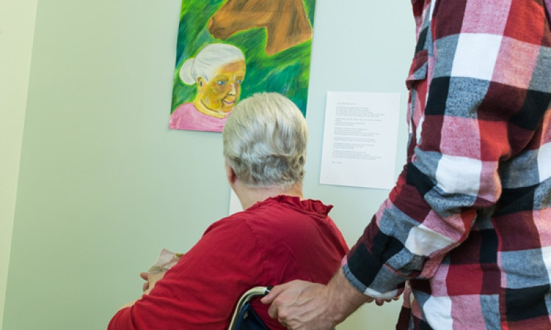Student and Resident at the art exhibit at Flint Ridge Nursing and Rehabilitation Center viewing a portrait of a women and horse