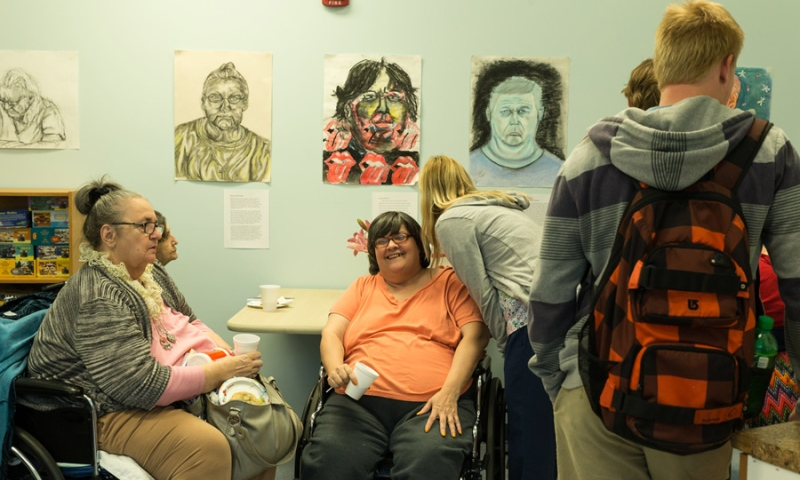 Students gathering around Residents of Flint Ridge Nursing and Rehabilitation Center sitting under their protraits