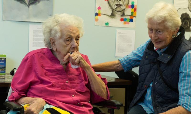 2 Residents of Flint Ridge Nursing and Rehabilitation Center gathering around the portraits