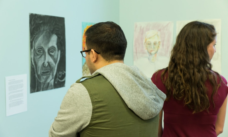 Students viewing 2 art pieces at Flint Ridge Nursing and Rehabilitation Center