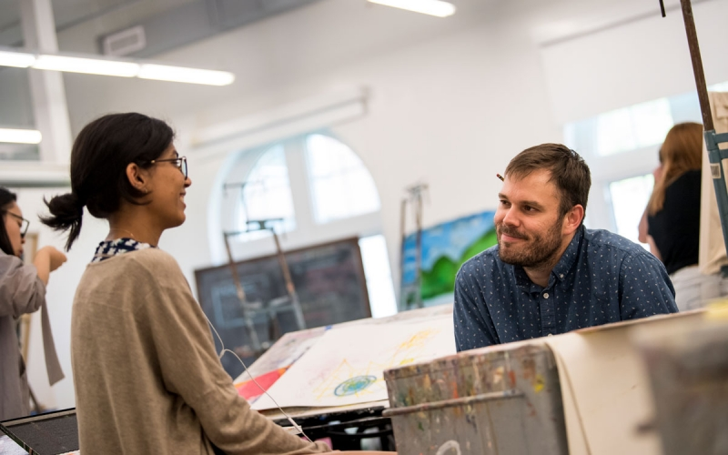 Student in conversation with professor Keith Spencer