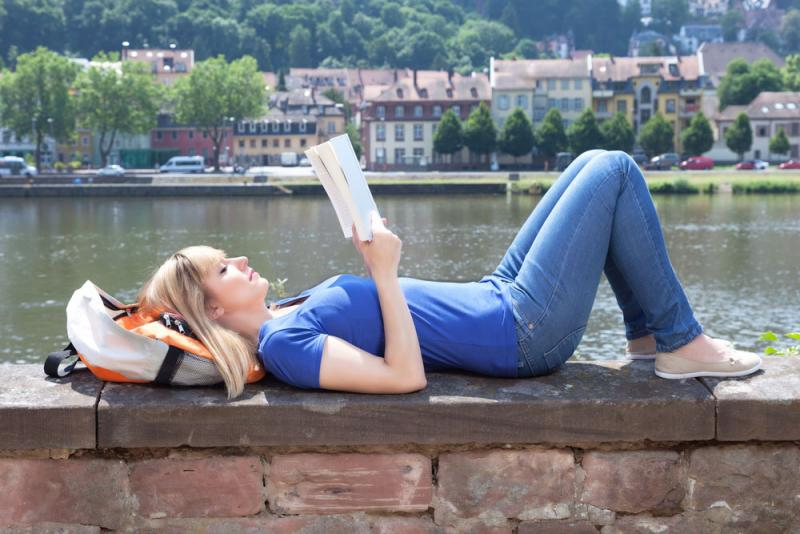 Student reading by a body of water