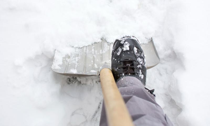 Foot pressing down on shovel in snow