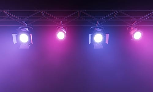 A photo of four stage lights against a dark background