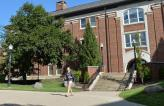Student walking out of Olin, the building that houses the physics department.