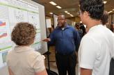 Students and professor discussing a research poster