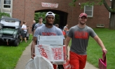 Football players helping people move in