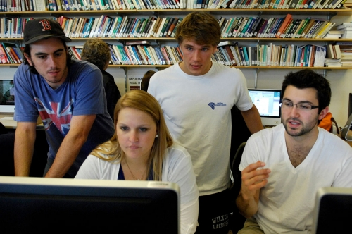students around a computer in discussion