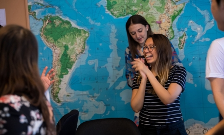 students beside world map