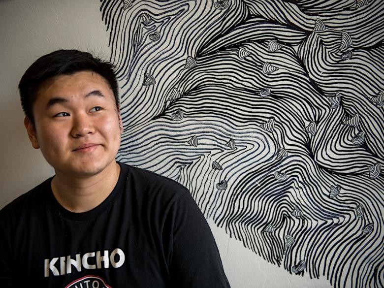 Studio Art student in front of his artwork