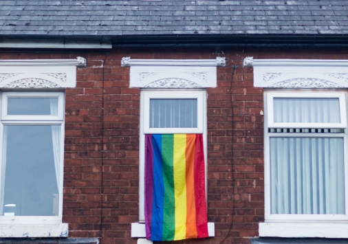 Pride flag hanging out of a window