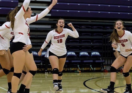 Julia Miller and teammates celebrate during a volleyball match