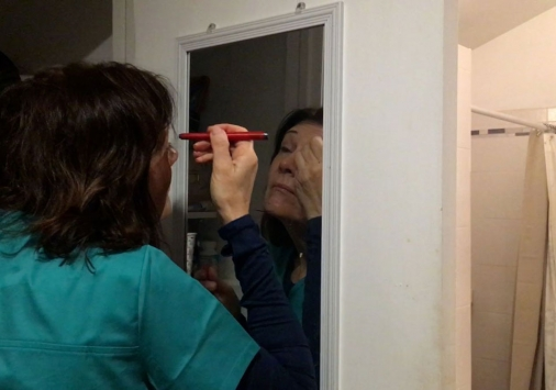 Woman in front of mirror putting on makeup