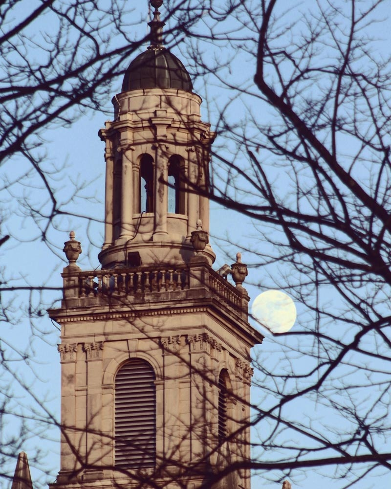 The top of Swasey Chapel seen through bare trees with the Moon rising in the background