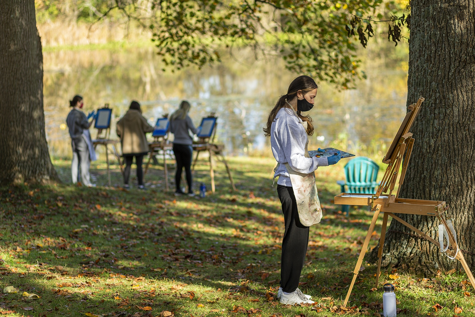 Students paint on easels outdoors while wearing masks